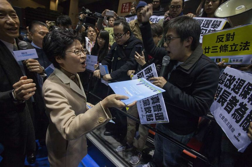 Carrie Lam (2nd from left), faces off against a group of pro-democracy protesters calling for real universal suffrage after launching her policy platform in Mong Kok, Hong Kong, China, on Feb 27, 2017.