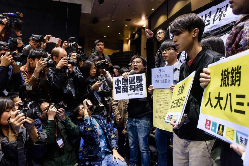 A group of protesters (right) shout slogans against former chief secretary and chief executive election candidate Carrie Lam (not seen) before the start of a press conference held by Lam in Hong Kong on Feb 27, 2017.
