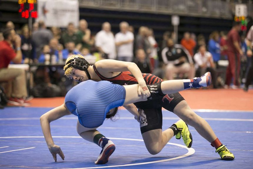 Transgender wrestler Mack Beggs, on top, takes on Taylor Latham in the opening round of the Texas girls' state tournament.