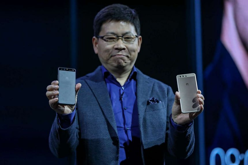 Mr Richard Yu, chief executive officer of Huawei Technologies, holding Huawei P10 smartphones during its launch, ahead of the Mobile World Congress in Barcelona, Spain, on Sunday (Feb 26).