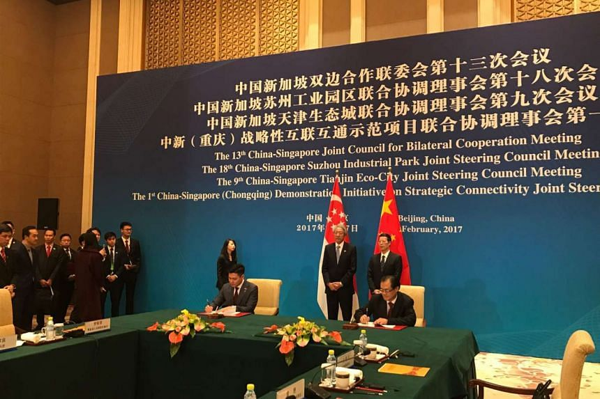 Mr Lee Ark Boon (seated left), CEO of IE Singapore, and Mr Liu Guiping, Vice-Mayor of Chongqing Municipal Government, sign a memorandum of understanding to facilitate the implementation of two commercial projects aimed at improving Chongqing's transp
