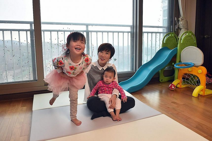 """Ms Kim, a 37-year-old IT engineer, and her daughters at their home in Seongnam, south of Seoul. She says she can """"totally relate"""" to the civil servant who died recently at the workplace shortly after resuming 12-hour workdays following her maternity"""