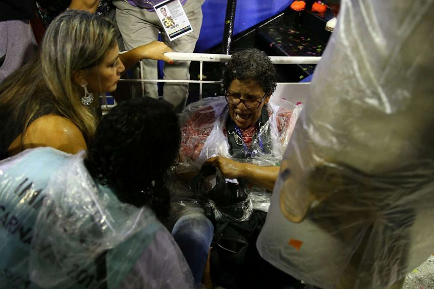 A photographer is assisted after an accident during the carnival parade at the Sambadrome in Rio de Janeiro, Brazil, on Feb 26, 2017.