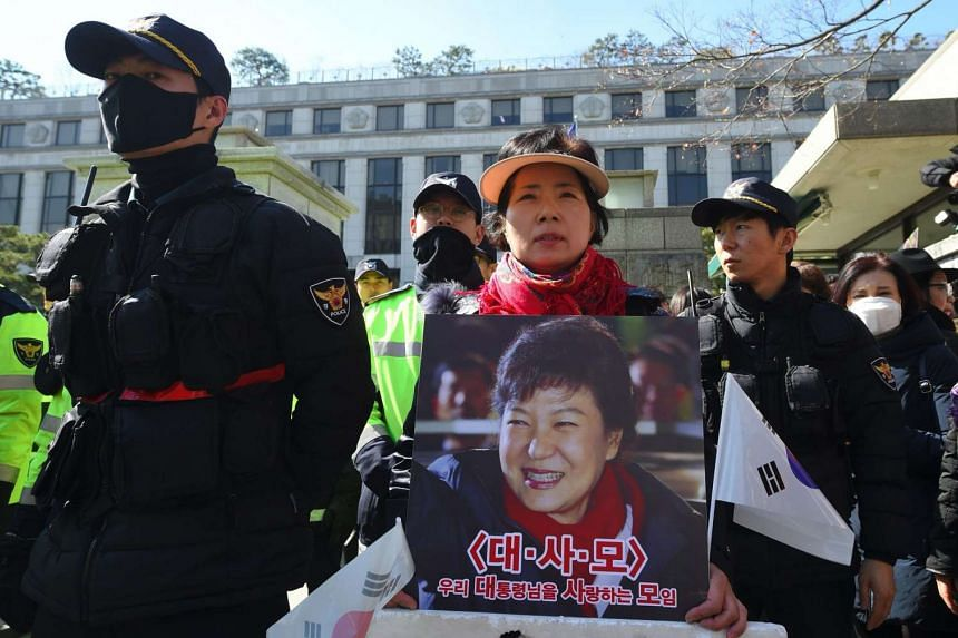 A pro-government activist holds a portrait of South Korean President Park Geun Hye outside the Constitutional Court in Seoul on Feb 27, 2017