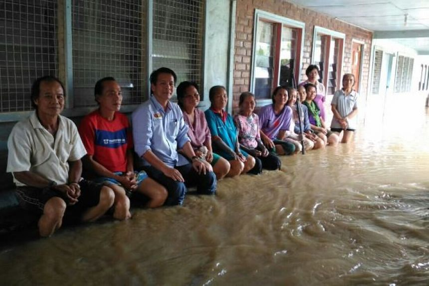 Mr Ngau (third from left) with the flood victims in one of the long houses.