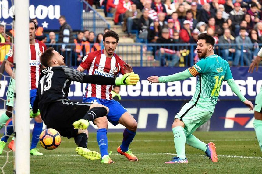 Lionel Messi (centre) scores against Club Atletico de Madrid in Madrid on Sunday (Feb 26, 2017).