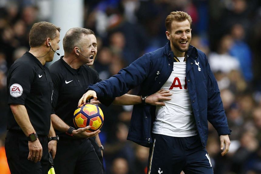Tottenham's Harry Kane takes the match ball from referee Jonathan Moss at the end of the match after completing a hat trick.