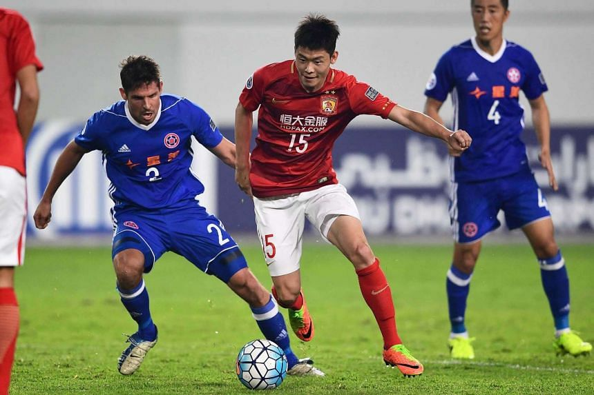 Zheng Wenzhao (centre) of Guangzhou Evergrande competing for the ball with Josh Mitchell of Eastern FC during their AFC Champions League group stage football match, on Feb 22, 2017.