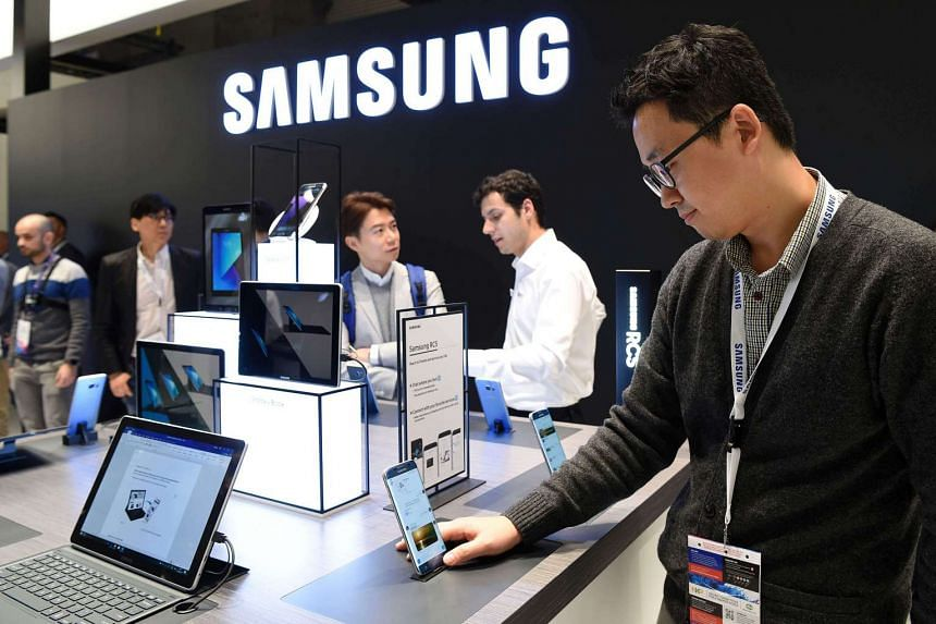 Visitors try devices at the stand of Samsung on the first day of the Mobile World Congress in Barcelona.