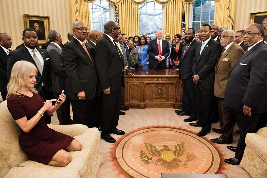 Counselor to the President Kellyanne Conway (L) checks her phone after taking a photo as US President Donald Trump and leaders of historically black universities and colleges pose for a group photo in the Oval Office of the White House on Feb 27, 201