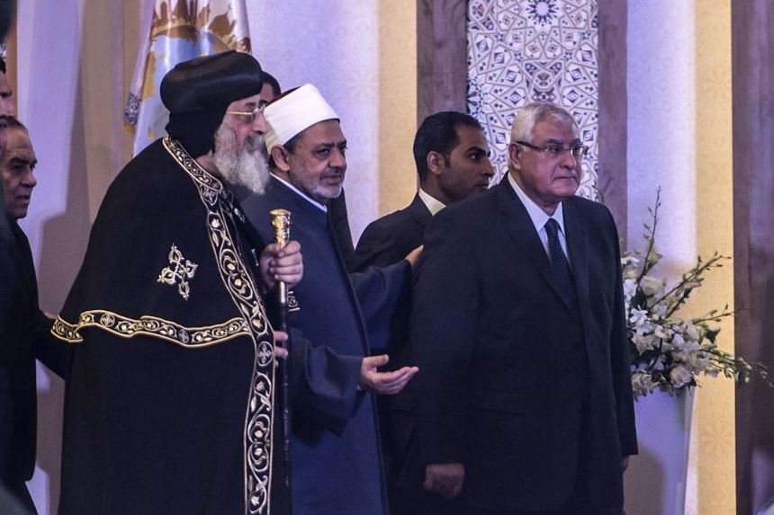 Egypt's Grand Imam of al-Azhar Sheikh Ahmed Mohamed al-Tayeb (centre), Egypt's former interim president Adly Mansour (right), and Pope Tawadros II (left) of Alexandria arrive to attend a conference titled ''Freedom and citizenship'' on Feb 28