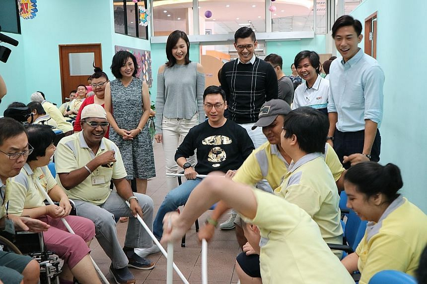 Actor Rayson Tan (seated, in black top) joins in a game with SPD beneficiaries. Looking on are celebrities (standing, from left): Michelle Tay, Xiang Yun, Ya Hui, Elvin Ng and Desmond Tan. Members of the SPD community will perform with celebrities du