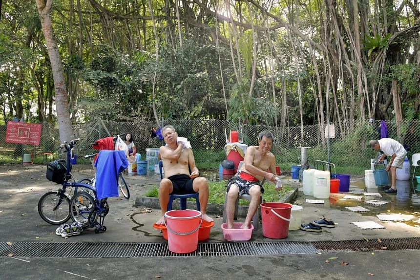 Visitors enjoy a relaxing foot soak (above and below) at the the hot spring. Some people wash their clothes there and regular visitors even padlock their buckets - and a metal bathtub - to the chain link fence. The hot spring sits in a military camp