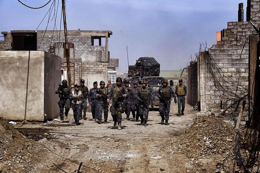 """Members of the Iraqi federal police on patrol in Mosul on Sunday. """"The street fighting is intense, these are populated neighbourhoods,"""" said Brigadier-General Yahya Rasool, spokesman for the Joint Operations Command directing Iraqi forces battling IS"""