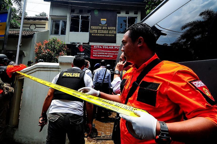 Police securing the area around the municipal office in Bandung, West Java, yesterday. Armed police officers outside the municipal office traded shots with a suspected terrorist following a bomb blast set off by two men earlier at a nearby park in Ba