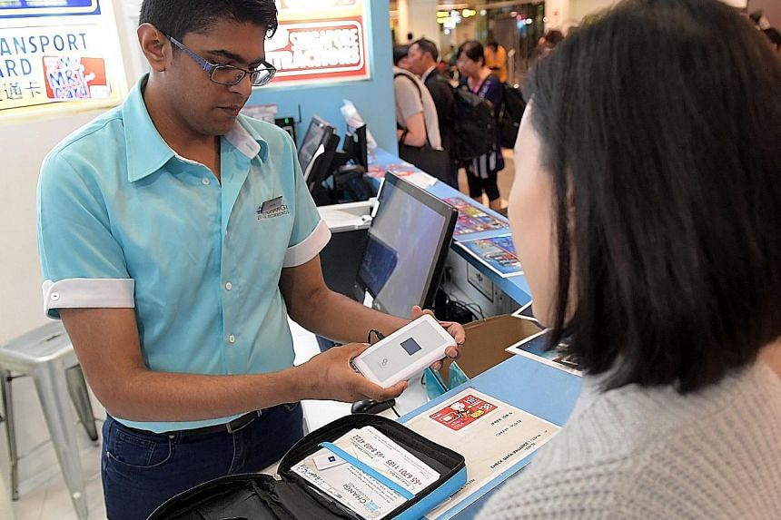 Above: Retail sales associate Jeryck Tan explaining to a customer how to use a Wi-Fi router at the Changi Recommends outlet in Terminal 1. The rental of such routers is a popular service that began in 2015. Left: There are eight Changi Recommends out