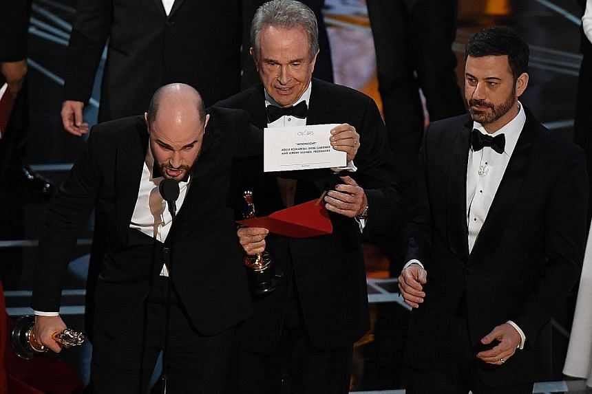 La La Land producer Jordan Horowitz holding up the card showing Moonlight as Best Picture winner, as presenter Warren Beatty (centre) and host Jimmy Kimmel look on.