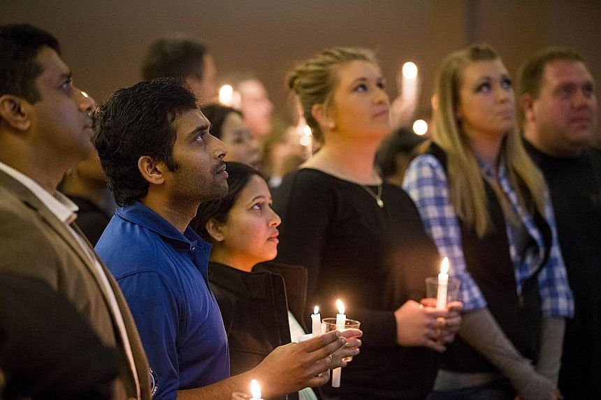 Around 1,000 people, including (from second from left) Mr Madasani, his wife, Ms Reepthi Gangula, and sisters of hero Ian Grillot, Laura and Maggie, at a prayer vigil in memory of Mr Kuchibhotla on Sunday.