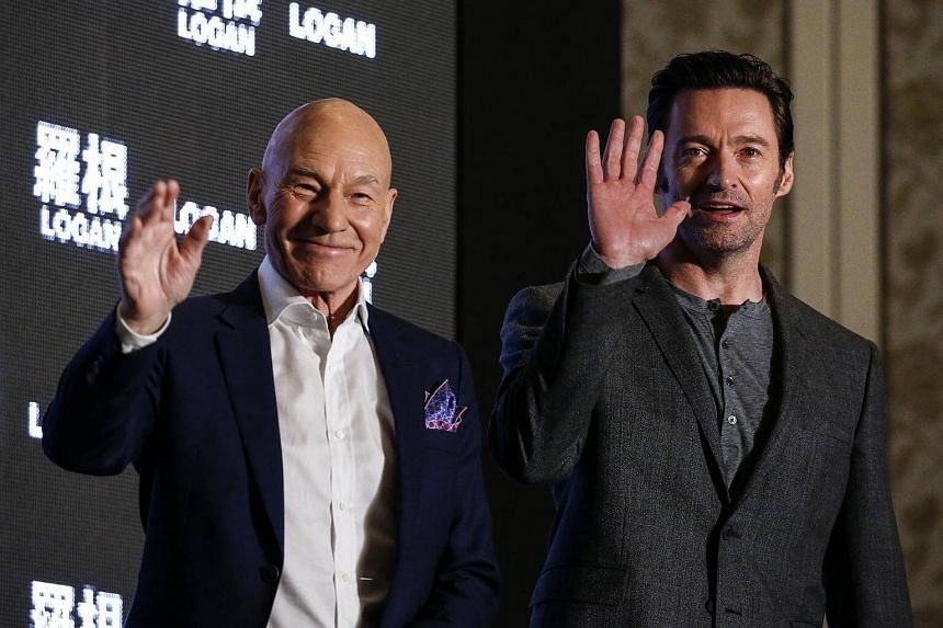 Australian actor Hugh Jackman (right) and British actor Patrick Stewart wave during a press conference for their first Asia movie premiere of Logan in Taipei.
