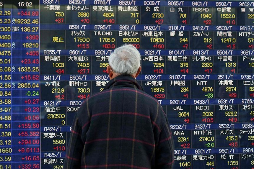 A pedestrian looks at an electric quotation board flashing stock prices on the Nikkei key index of the Tokyo Stock Exchange in Tokyo.