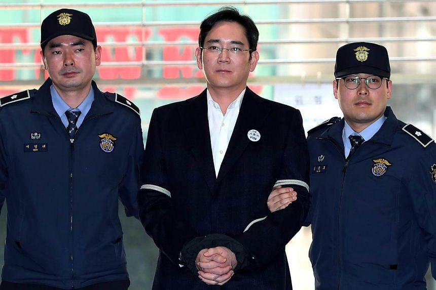 Lee Jay Yong is escorted by police officers as he arrives at the special prosecutors' office for questioning in Seoul.