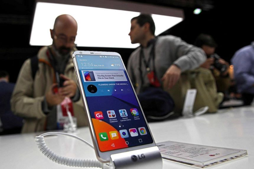 Visitors discuss the new device behind the new smartphone LG G6 during its presentaton on the eve of the opening of Mobile World Congress (MWC) in Barcelona, northeastern Spain, on 26 Feb 2017.