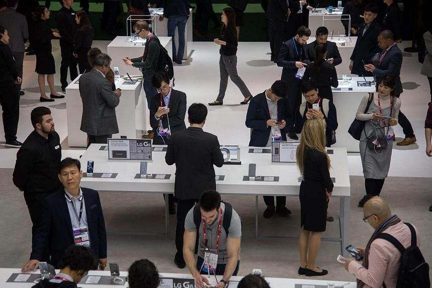Visitors test various LG devices at company's booth during the Mobile World Congress on the first day of the MWC in Barcelona, on Feb 27, 2017.
