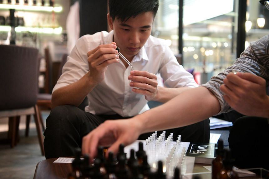 Straits Times reporter Raynold Toh tries his hand at mixing fragrance nodes to create different scents during a workshop on Feb 28, 2017.