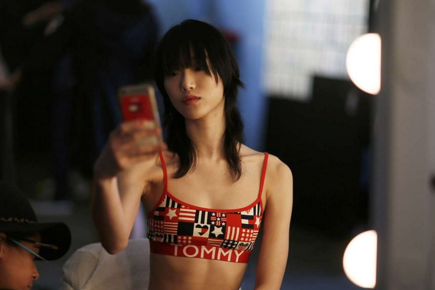 A model prepares in front of a cell phone at the 2017 Tommy Hilfiger Runway Show in Venice, California, on Feb 8, 2017.