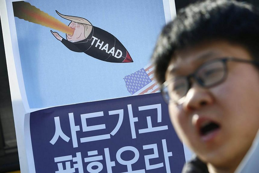A South Korean protester shouts slogans in front of a placard reading 'Thaad out' during a rally against the South Korean and US Government's defense policy in front of the Ministry of National Defense in Seoul.