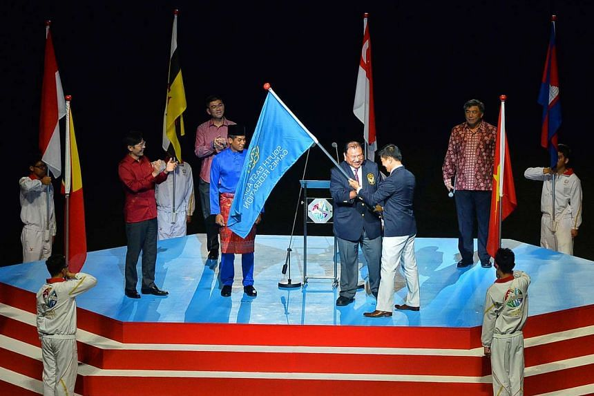 Tunku Imran receives the SEA Games Federation flag from Singapore National Olympic Council president Tan Chuan-Jin at the closing ceremony of the 28th SEA Games at National Stadium in 2015.