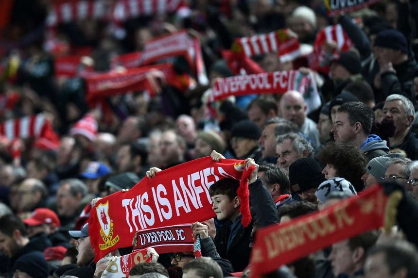 Liverpool supporters raise their scarves in the crowd ahead of the English Premier League football match between Liverpool and Tottenham Hotspur at Anfield, on Feb 11, 2017.