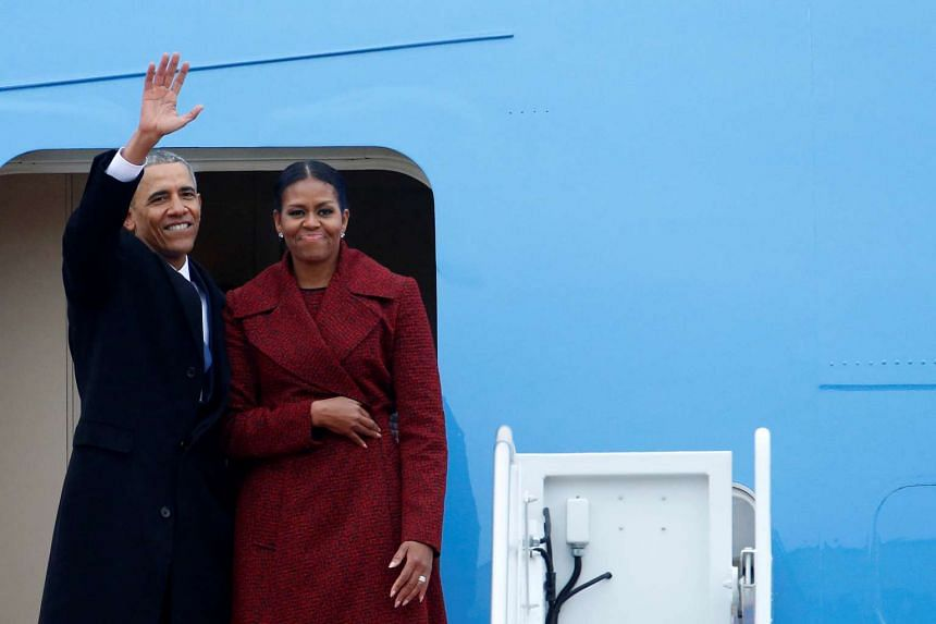 Former president Barack Obama waving with his wife Michelle as they board Special Air Mission 28000, on Jan 20, 2017.