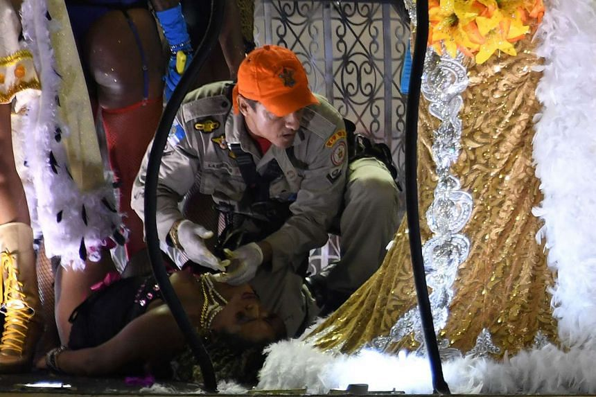 A firefighter assists a reveller of the Unidos da Tijuca samba school after the third floor of a float collapsed.
