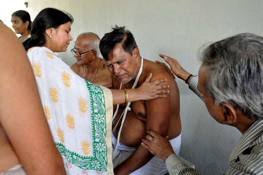 The victim's father, Mr K. Madhusudhana Sastry (second right), is consoled during his son's funeral.