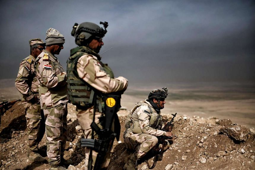 Members of the Iraqi army's 9th Division hold a position on a hill in Talul al-Atshana, on the southwestern outskirts of Mosul, on Feb 27, 2017, during an offensive to retake the city from Islamic State in Iraq and Syria group fighters.