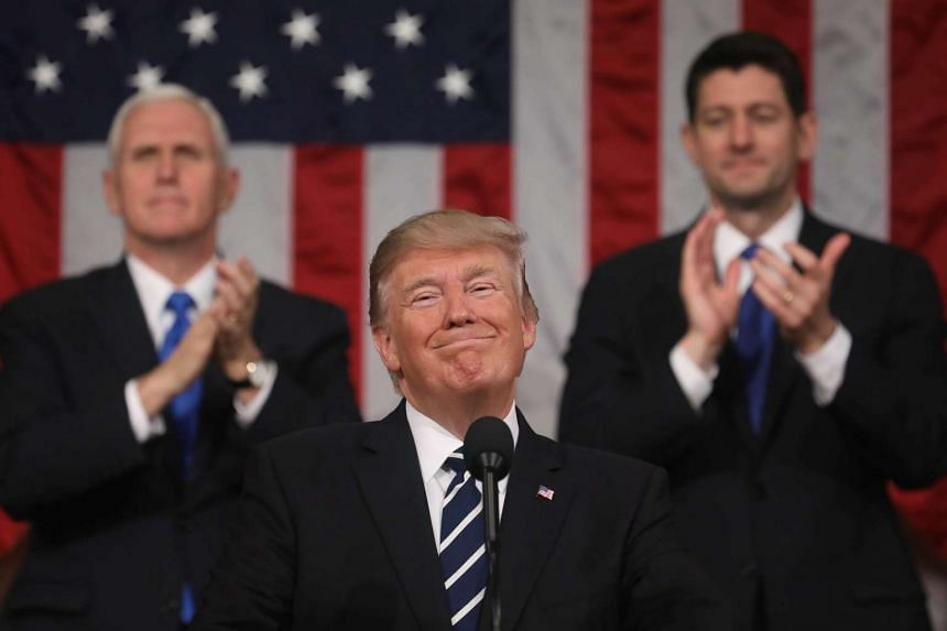 US President Donald Trump (centre) is applauded while delivering his first address to a joint session of Congress from the floor of the House of Representatives in Washington, DC.