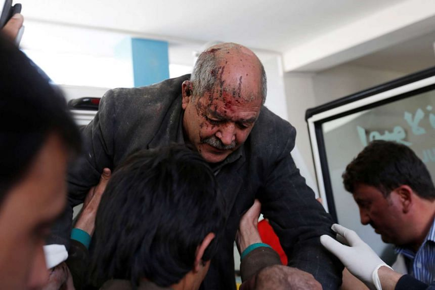 Men carry an injured man to a hospital after attacks in Kabul, March 1, 2017.