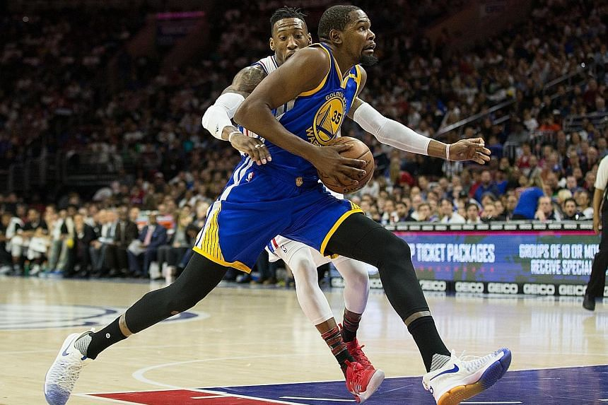 Golden State Warriors forward Kevin Durant outpaces Robert Covington of the Philadelphia 76ers during the 119-108 victory Durant led the Warriors with 27 points, while Klay Thompson contributed 21.