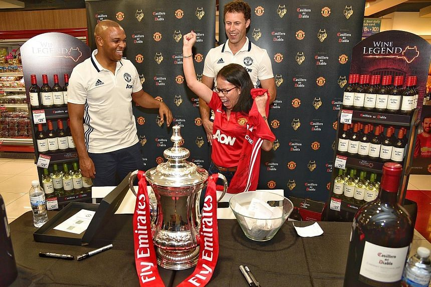 Manchester United fan Lea Cambel, the winner of the lucky draw, celebrates as she gets a club jersey while former players Quinton Fortune (left) and Ronny Johnsen look on at Plaza Singapura yesterday. The duo are in Singapore to promote a brand of wi