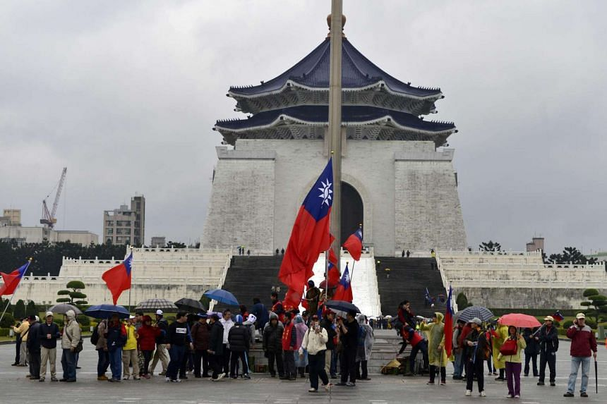 Pro-unification activists raising a Taiwanese flag in front of the Chiang Kai-shek Memorial Hall during the 70th anniversary of the 228 incident in Taipei on Feb 28, 2017.