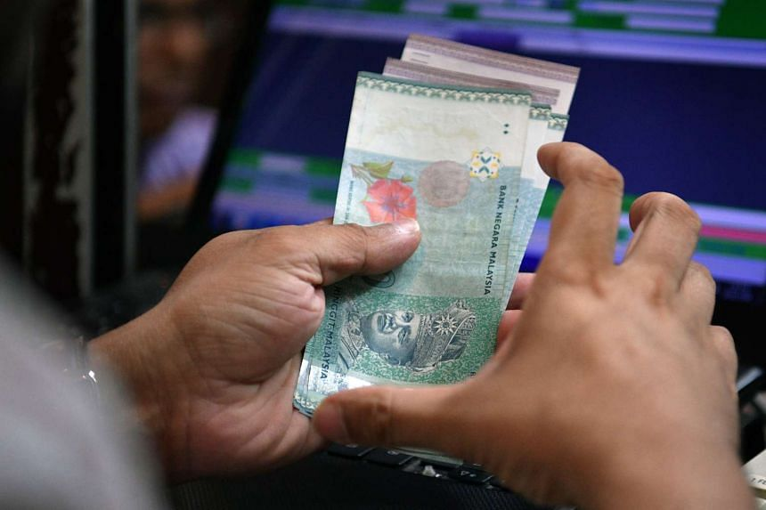 An employee at a Change Alley money changer counting a wad of Malaysian ringgit banknotes.
