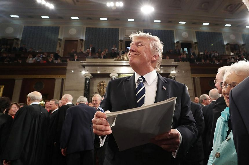 US President Donald Trump signs an autograph on his way out after delivering his first address to a joint session of Congress.