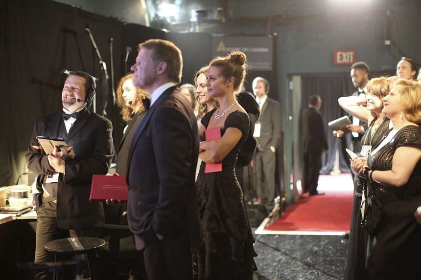 Brian Cullinan (foreground) holds a stack of red envelopes backstage during the Academy Awards.