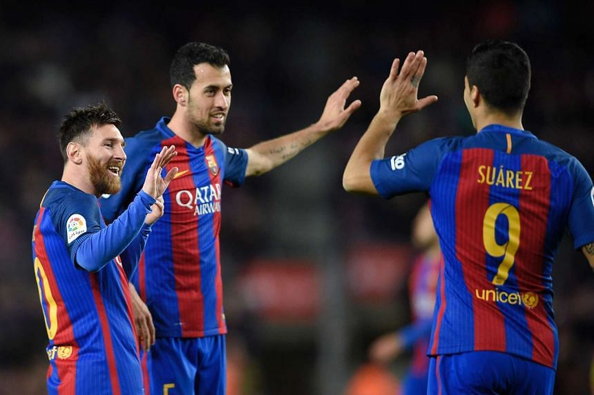 Barcelona's Lionel Messi (left) celebrates with teammates Sergio Busquets (centre) and Luis Suarez after scoring during their Spanish league football match against Real Sporting de Gijon on March 1, 2017.