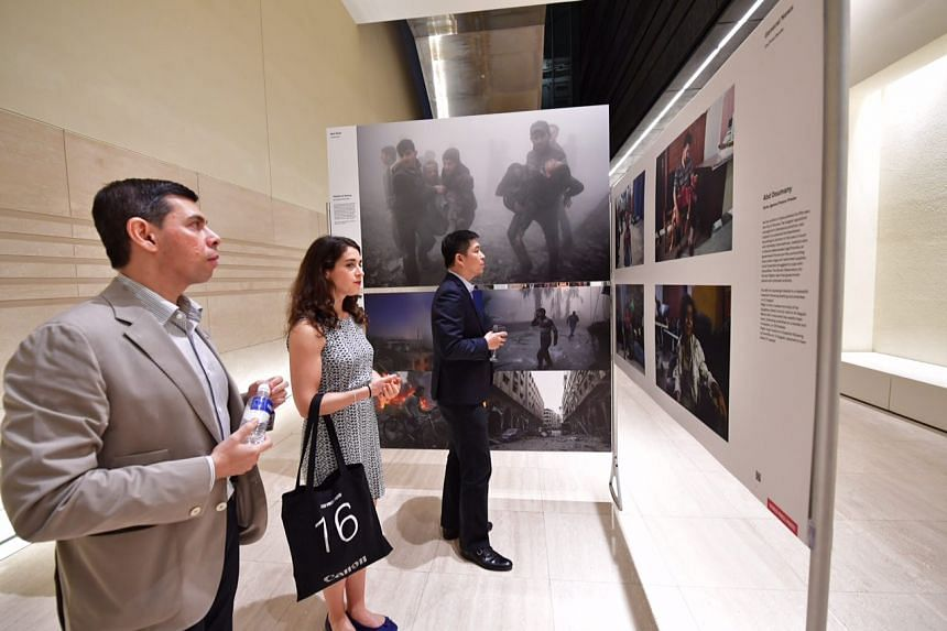 (From left) The Straits Times editor Warren Fernandez, World Press Photo exhibitions manager and curator Babette Warendorf and Minister for Social and Family Development Tan Chuan-Jin at the launch of the World Press Photo exhibition on March 2, 2017