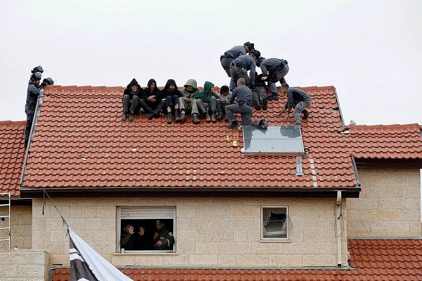 Israeli police removing pro-settlement activists from a roof yesterday. Israeli forces were carrying out a court order to demolish nine houses built illegally on privately owned Palestinian land in the Israeli settlement of Ofra, in the occupied West