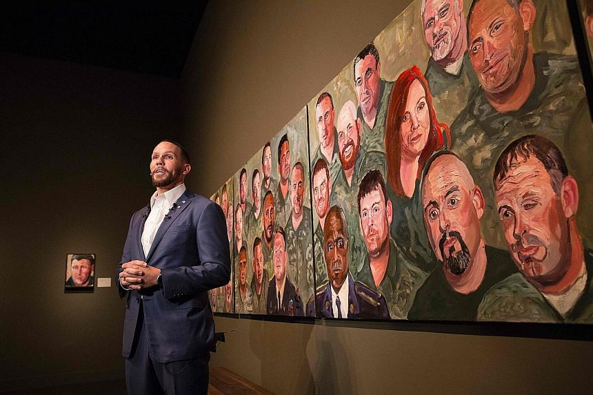 US Air Force Staff Sergeant Johnnie Yellock (right) in front of a painting of him by former United States president George W. Bush for the Portraits Of Courage exhibit at the George W. Bush Presidential Library and Museum in Dallas, Texas. On Tuesday