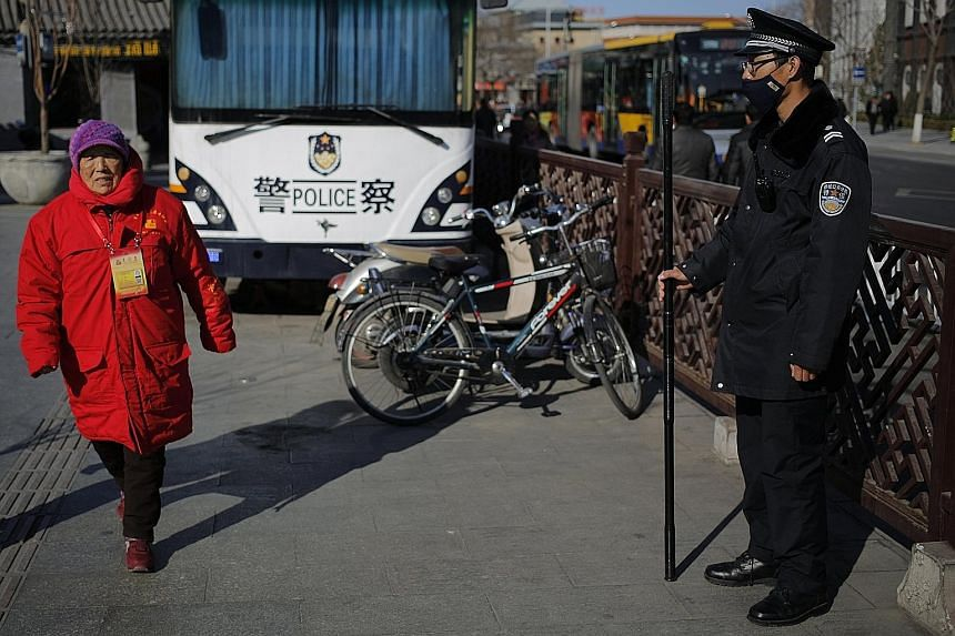 A public security volunteer and a security guard in Beijing yesterday. Security has been beefed up in the Chinese capital ahead of the country's annual parliamentary and consultative sessions.