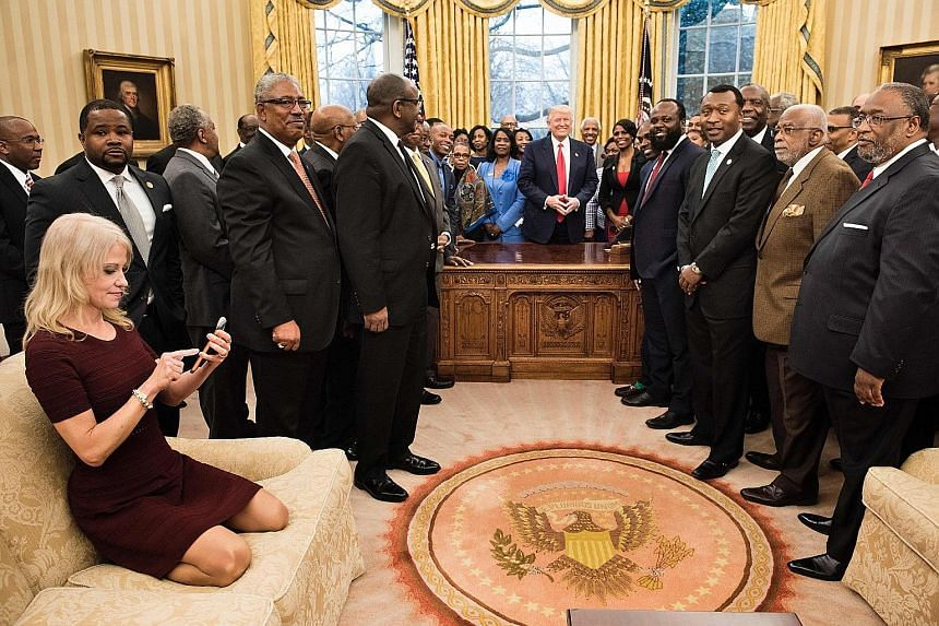 Ms Kellyanne Conway checks her phone soon after kneeling down on an Oval Office couch to take a photo of Mr Donald Trump and leaders of historically black universities and colleges in the US.
